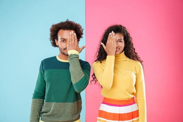 Retrato de hermosa pareja joven afroamericana cubrió las mitades de sus rostros con las manos sobre fondo de colores