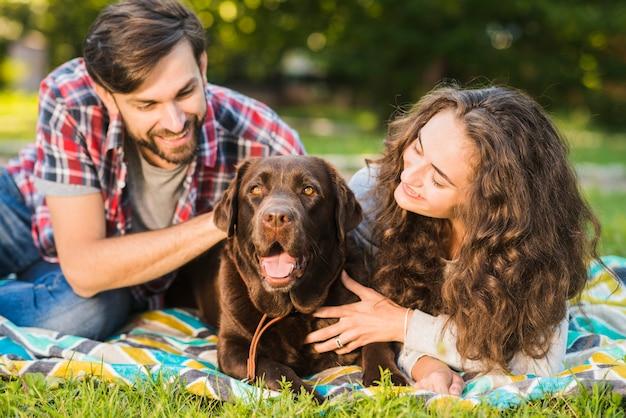 Retrato de una hermosa pareja joven con su perro en el jardín