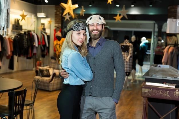 Retrato de una hermosa pareja en una máscara para dormir en una tienda de ropa