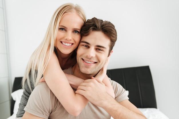 Retrato de hermosa pareja mirando en la cama