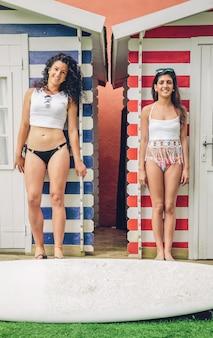 Retrato de hermosa pareja de mujeres surfistas con bikini y tabla de surf de pie sobre un fondo de cabañas de rayas de playa. concepto de ocio de verano.