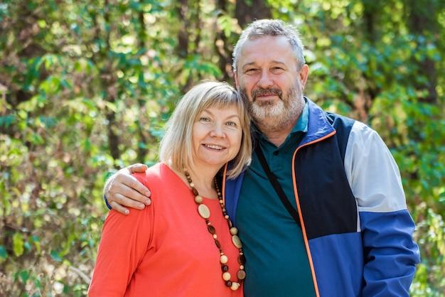 Retrato de hermosa pareja senior relajante en el parque de otoño
