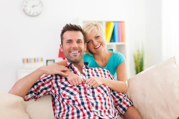 Retrato de hermosa pareja sonriente en casa