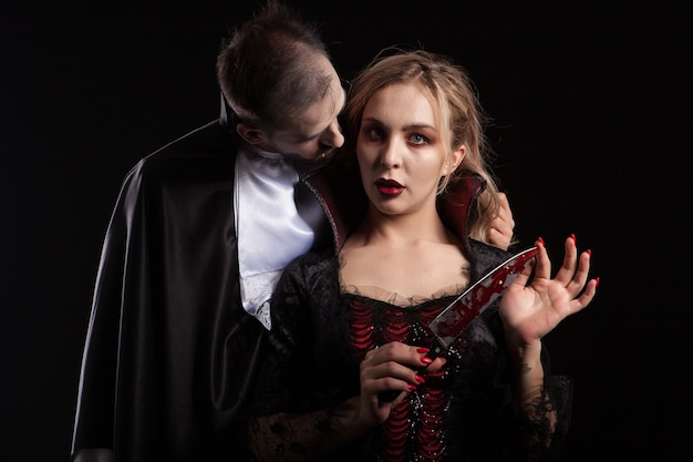 Retrato de una hermosa pareja en trajes medievales con maquillaje estilo vampiro para halloween. encantadora mujer vampiro.