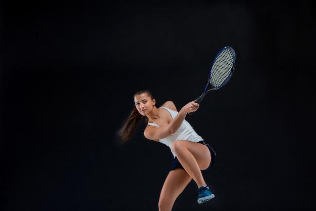 Retrato de la hermosa tenista con una raqueta en la pared oscura