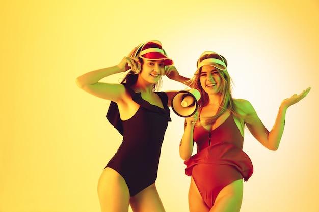Retrato de hermosas chicas jóvenes aislado sobre fondo amarillo estudio en luz de neón. mujeres en monos de moda. expresión facial, verano, fin de semana, belleza, concepto de resort. vacaciones, juventud.