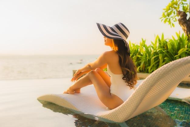 Retrato hermosas mujeres asiáticas jóvenes feliz sonrisa relajarse alrededor de la piscina al aire libre