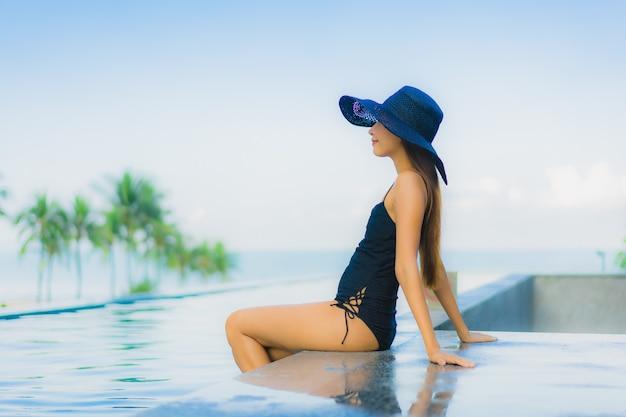 Retrato hermosas mujeres asiáticas jóvenes feliz sonrisa relajarse piscina al aire libre en el hotel