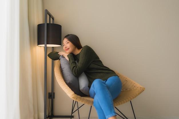 Retrato hermosas mujeres asiáticas jóvenes feliz sonrisa relajarse sentado en el sillón