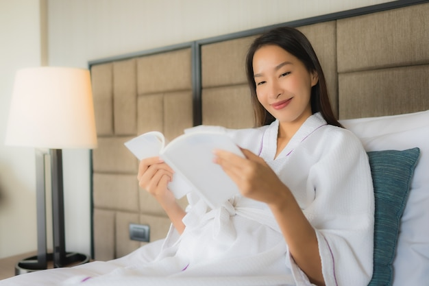 Retrato hermosas mujeres asiáticas jóvenes con libro sobre la cama