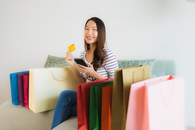 Retrato hermosas mujeres asiáticas jóvenes con tarjeta de crédito teléfono móvil o computadora para ir de compras