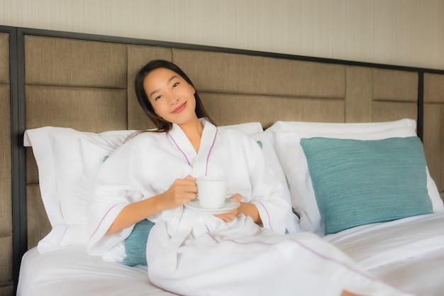 Retrato hermosas mujeres asiáticas jóvenes con taza de café en la cama