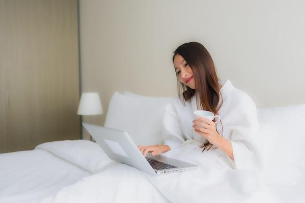 Retrato hermosas mujeres asiáticas jóvenes con taza de café y computadora portátil en la cama