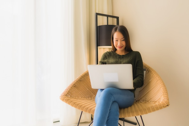 Retrato hermosas mujeres asiáticas jóvenes usando la computadora o computadora portátil para trabajar y sentarse en la silla del sofá