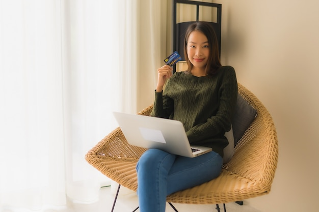 Retrato hermosas mujeres asiáticas jóvenes usando la computadora portátil con tarjeta de crédito para compras en línea