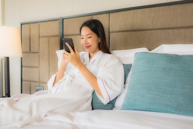 Retrato hermosas mujeres asiáticas jóvenes usando el móvil en la cama
