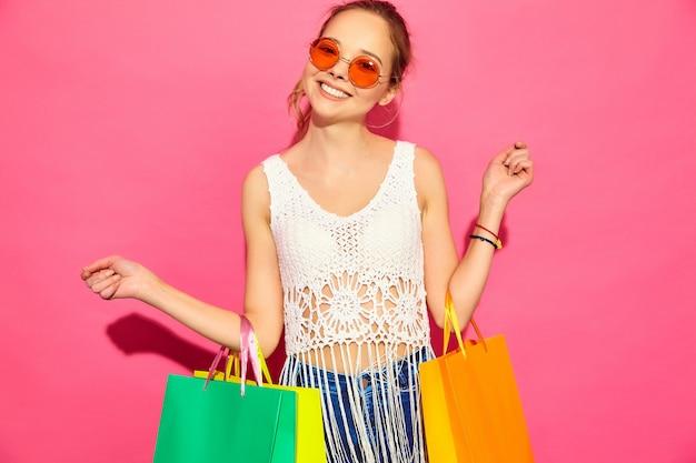 Retrato de hermosas mujeres compradoras sonrientes con bolsas de papel de colores. mujeres rubias que presentan en la pared rosada después de hacer compras. modelo positivo