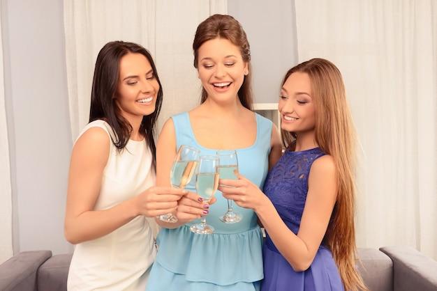 Retrato de hermosas mujeres de fiesta y sosteniendo copas con vino