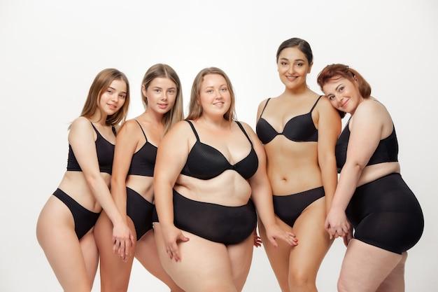 Retrato de hermosas mujeres jóvenes con diferentes formas posando en blanco