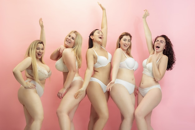 Retrato de hermosas mujeres jóvenes de talla grande posando en rosa