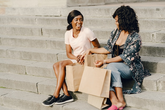 Retrato de hermosas mujeres negras jóvenes con bolsas de la compra.