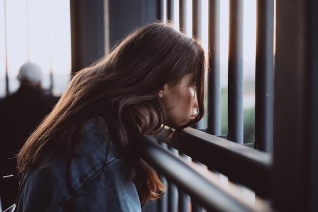 Retrato hermoso de la chica joven detrás de una cerca de hierro