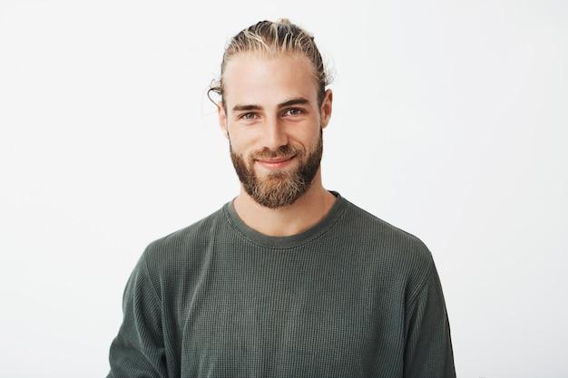 Retrato de un hermoso chico barbudo rubio maduro con peinado de moda en camisa gris informal sonriendo