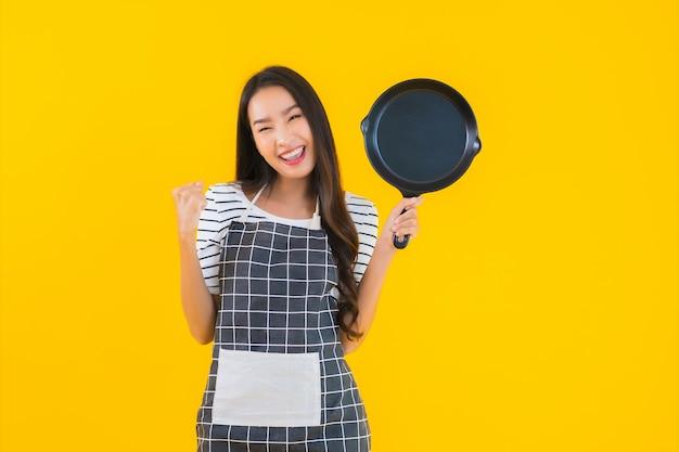 Retrato hermoso delantal de desgaste de mujer asiática joven con pan negro y espátula