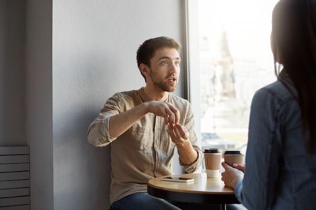 Retrato del hermoso diseñador independiente sin afeitar, sentado en un café en una reunión con un cliente que intenta explicar la concepción de su trabajo y expresivo gesticulando con las manos.