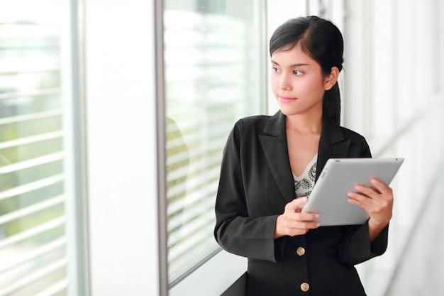 Retrato hermoso de la empresaria usando la tableta