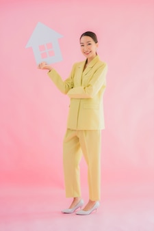 Retrato hermoso joven asiático mujer de negocios mostrar casa o signo de casa en color aislado