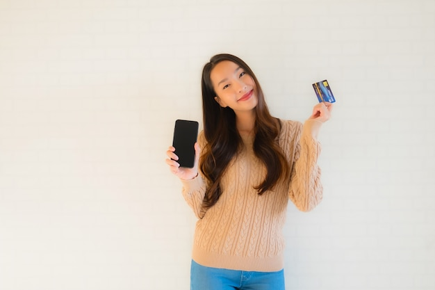 Retrato hermoso joven asiático uso teléfono móvil inteligente con tarjeta de crédito