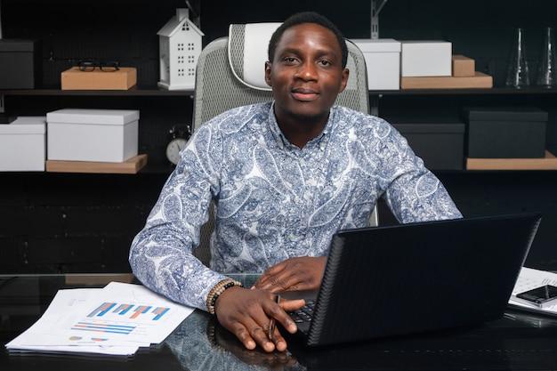 Retrato de hermoso joven empresario afroamericano que trabaja con documentos y computadora portátil en la oficina