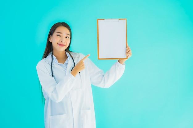 Retrato hermoso joven médico asiático mujer con cartón vacío