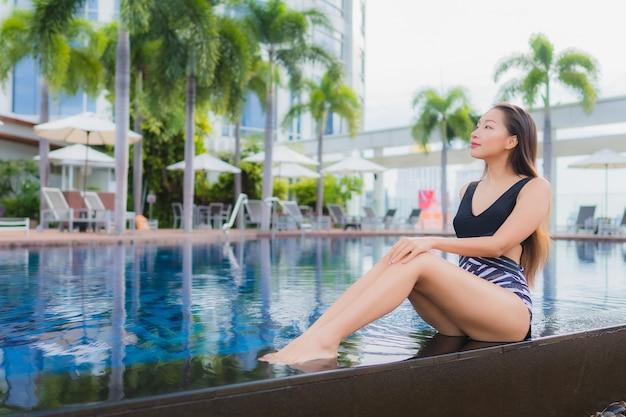 Retrato hermoso joven mujer asiática ocio relajarse sonreír alrededor de la piscina al aire libre para vacaciones