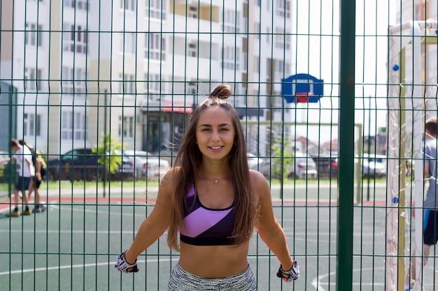 Retrato hermoso joven de la mujer en una cancha de básquet