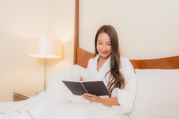 Retrato hermoso libro de lectura de la mujer asiática joven en la cama en el interior del dormitorio