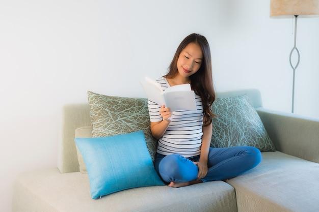 Retrato hermoso libro de lectura de mujeres asiáticas jóvenes con taza de café