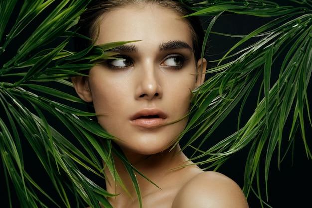 Retrato hermoso de la mujer en arbustos de palma, piel hermosa de la cara