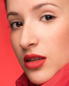 Retrato hermoso de la mujer en fondo rojo