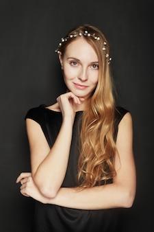 Retrato hermoso de la mujer joven en fondo negro