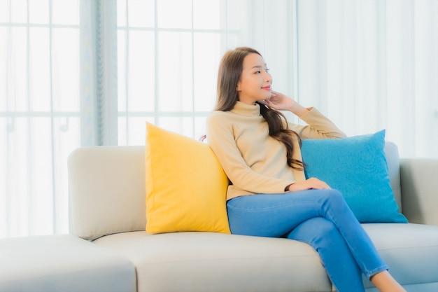 Retrato, de, hermoso, mujer joven, en, sofá, en, sala
