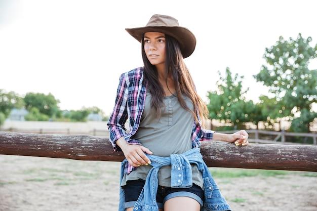Retrato, de, hermoso, mujer joven, vaquera, en, sombrero, y, camisa a cuadros