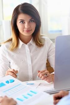 Retrato hermoso de la mujer en el lugar de trabajo que examina estadísticas financieras