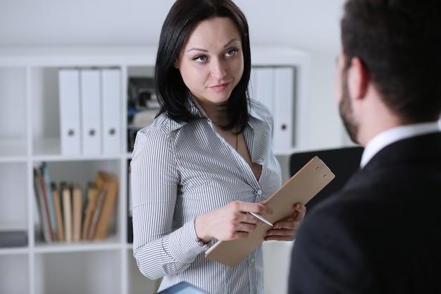Retrato hermoso de la mujer en el lugar de trabajo que examina estadísticas financieras.