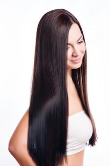 Retrato hermoso de la mujer morena con el pelo sano