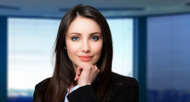 Retrato hermoso de la mujer de negocios en su oficina
