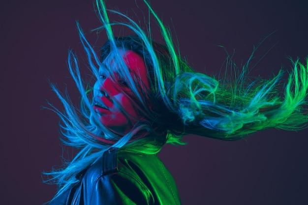 Retrato hermoso de la mujer con el pelo que sopla en la luz de neón colorida