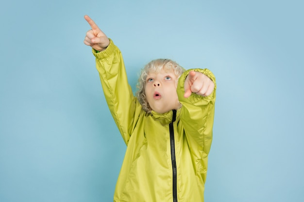 Retrato de hermoso niño caucásico aislado sobre fondo azul de estudio. modelo masculino rubio rizado. concepto de expresión facial, emociones humanas, infancia, publicidad, ventas.
