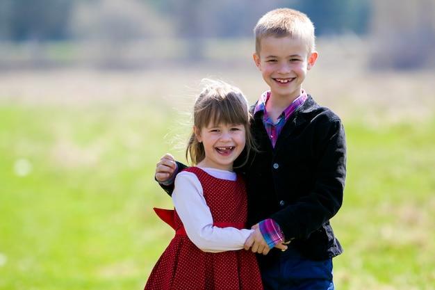 Retrato de hermosos niños rubios sonrientes con divertidos dientes infantiles en ropa elegante de pie juntos al aire libre